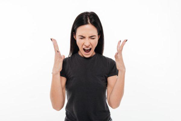 mulher irritada com TPM devido a distúrbio hormonal