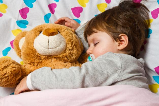 Criança dormindo com ursinho de pelúcia