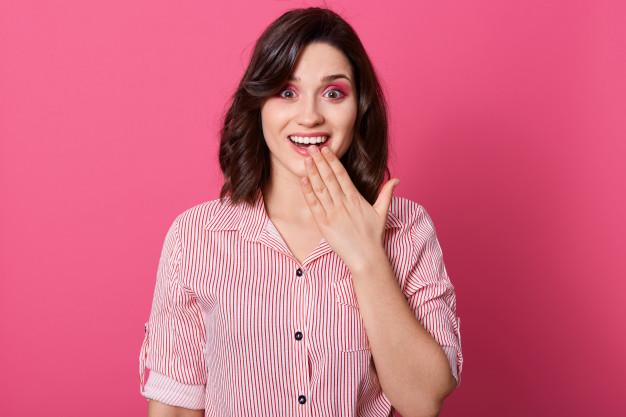 Mulher com a mão na boca sorrindo