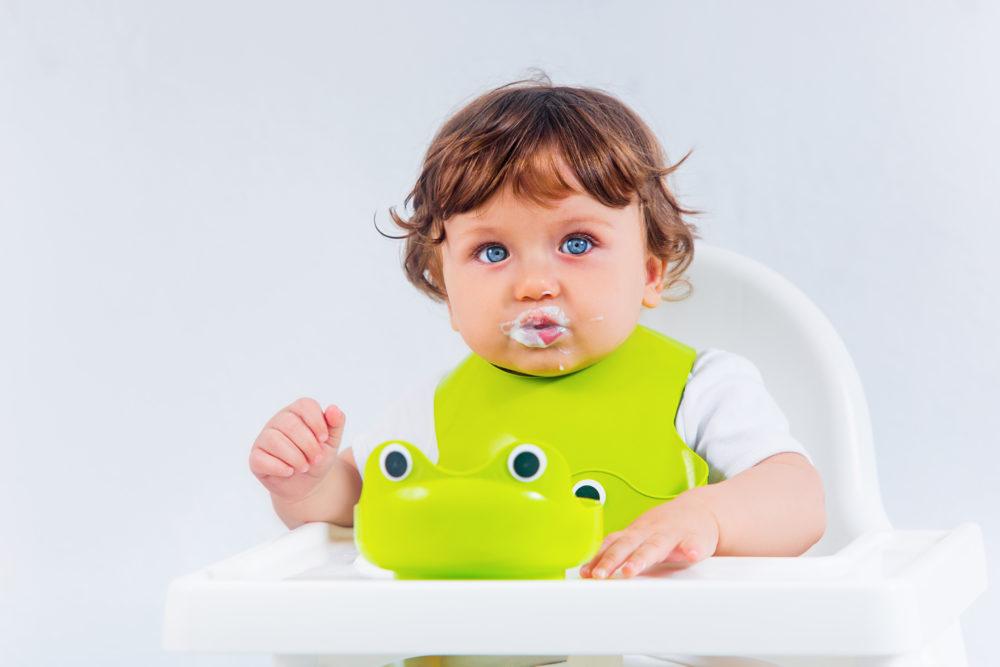 Bebê na cadeira com a boca toda branca