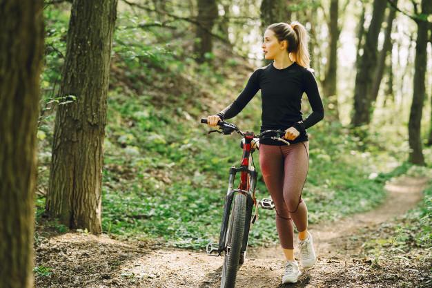 Mulher empurrando a bicicleta