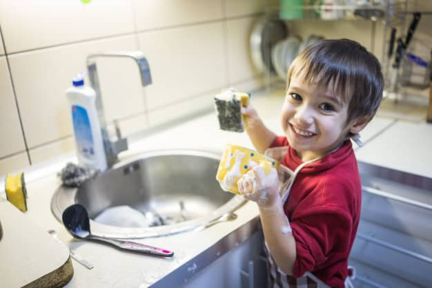 Menino pequeno de blusa vermelha lavando caneca amarela