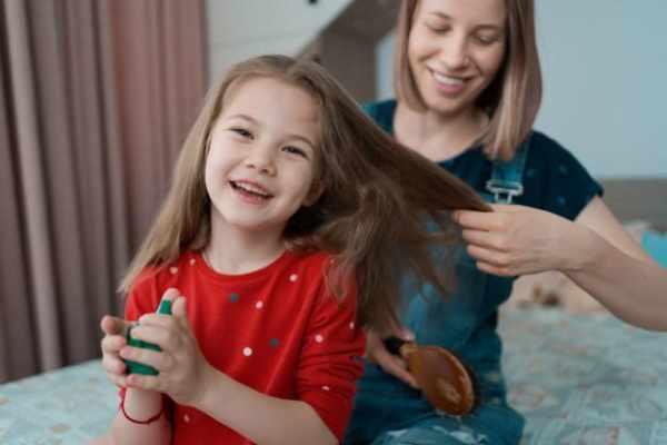 Mulher penteando cabelo de sua filha