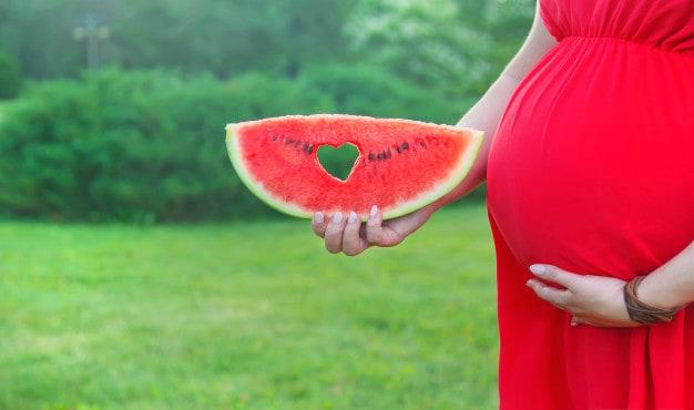 Mulher gravida com vestido vermelho e melancia na mão