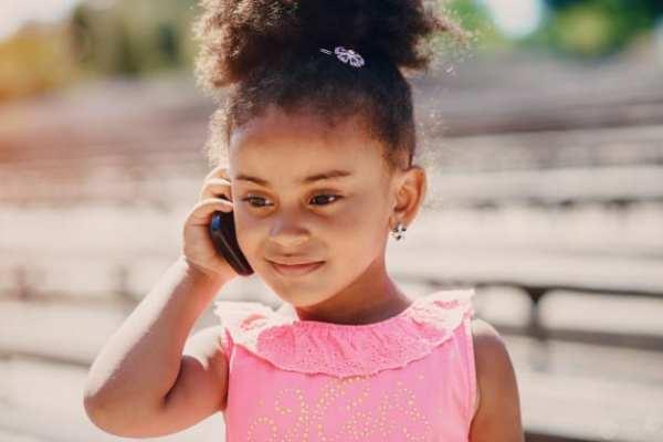 Criança falando ao telefone