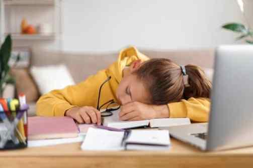 criança dormindo sob a mesa de estudos