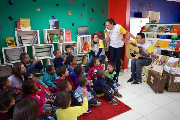 A group of volunteers and children singing