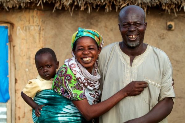 Parents and their baby smiling at home in northern Ghana, Africa