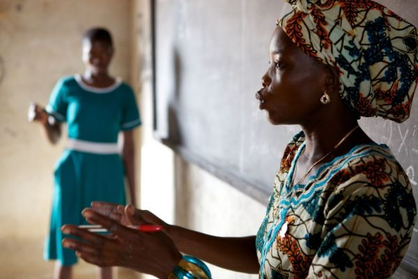 A teacher talking at the front of a classroom, Ghana.