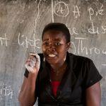 A teacher teaching a class in front of the black board, Ghana, Africa