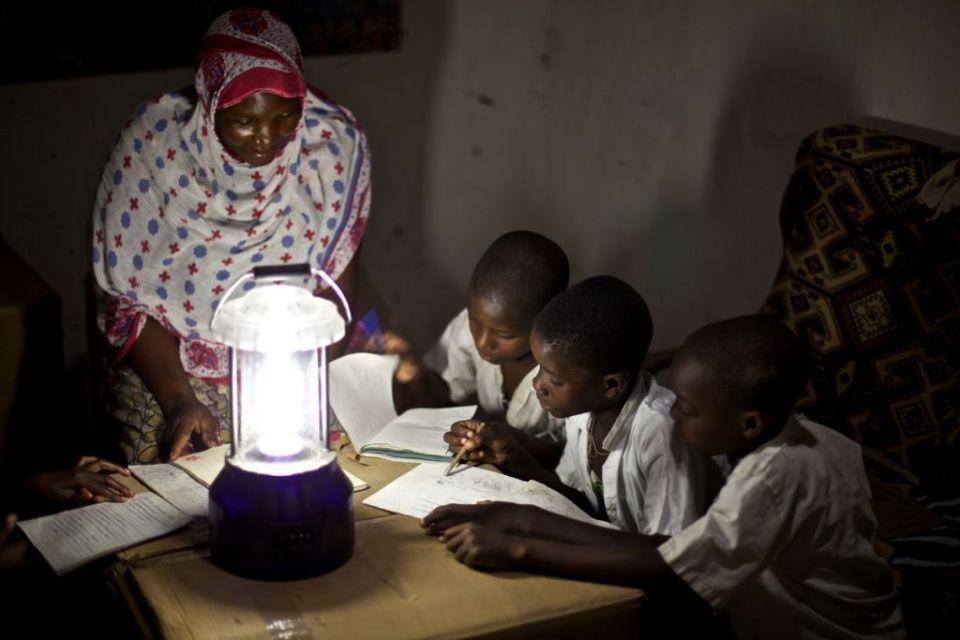 A teacher teaches by solar powered lantern, Tanzania.