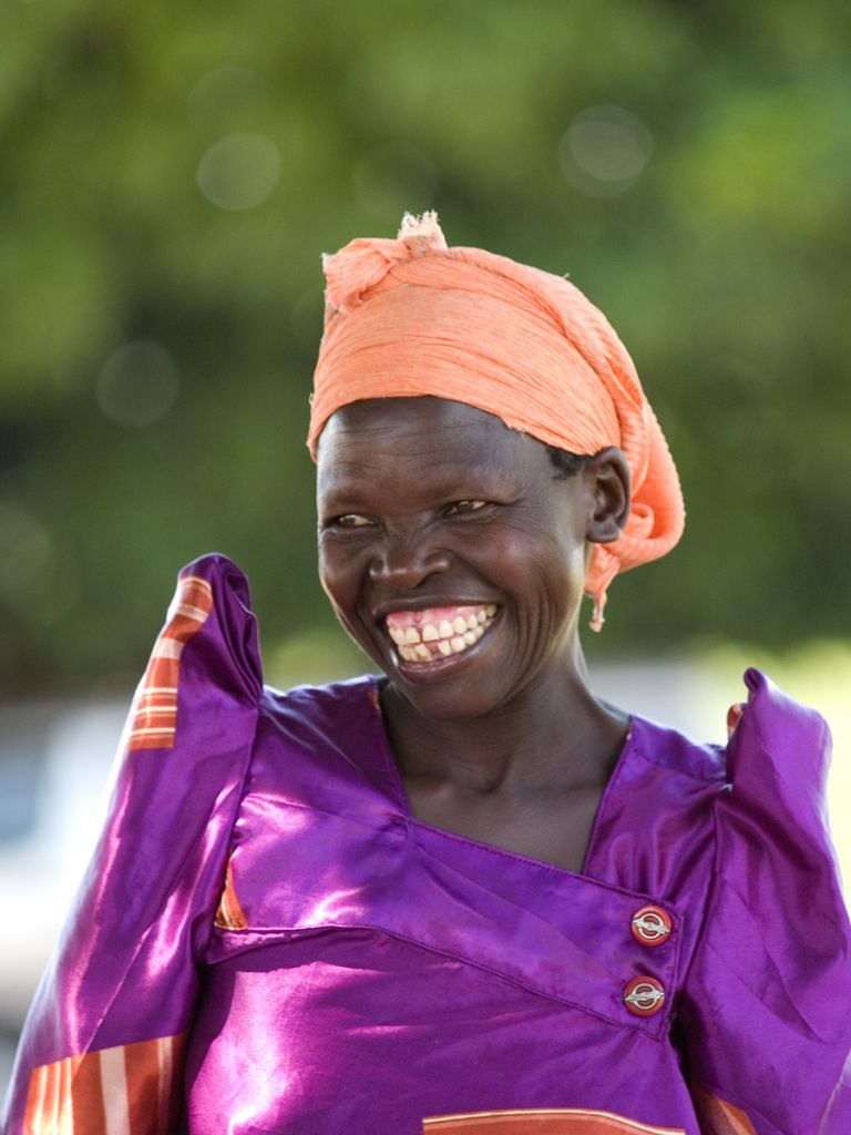 A lady wearing an orange headscarf with a huge smile, Uganda.