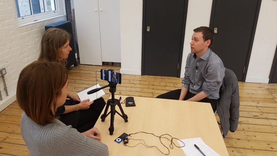 an interview taking place with three people and a smartphone on a tripod.