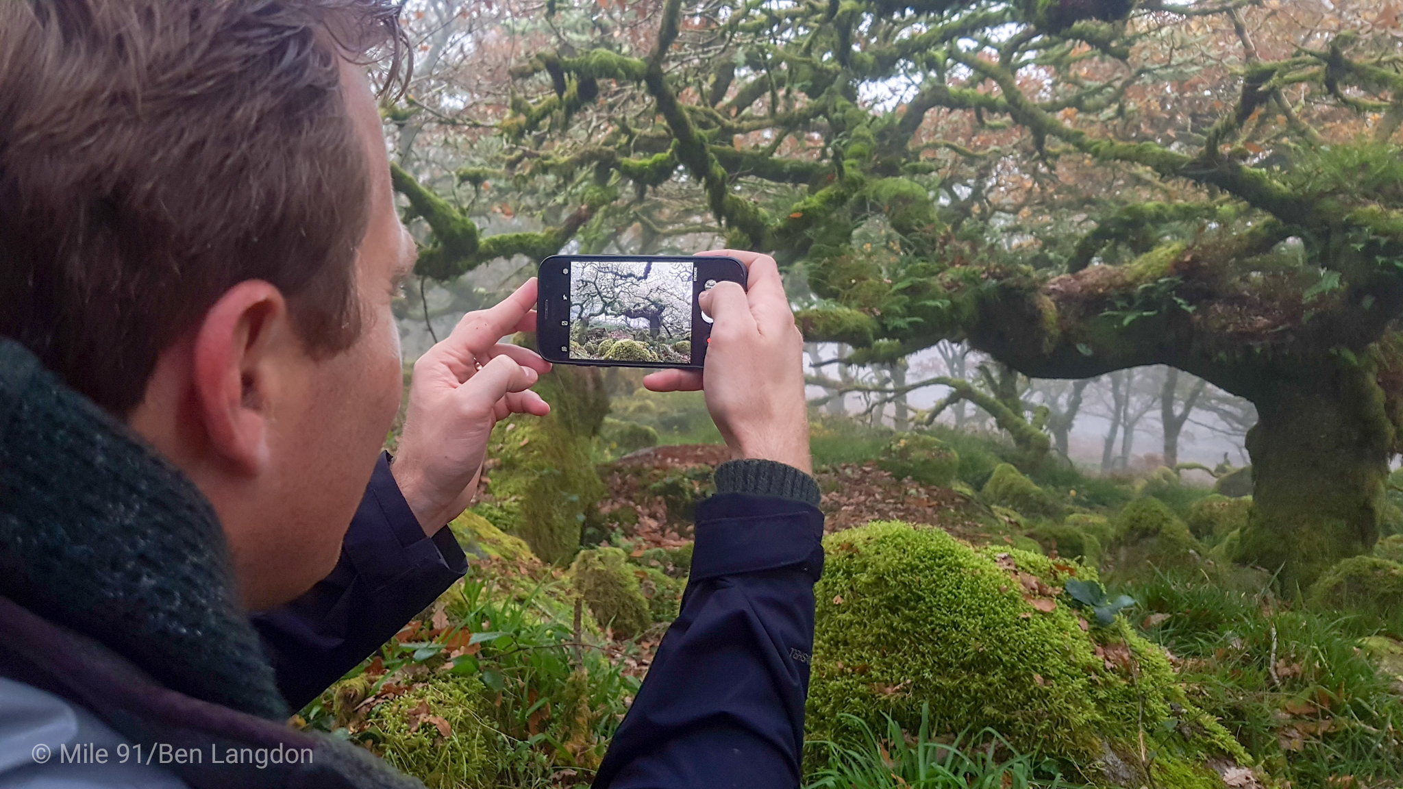 man gathering stories filming in Dartmoor with smartphone