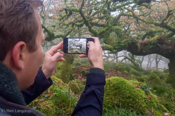 man gathering stories filming in Dartmoor with smartphone
