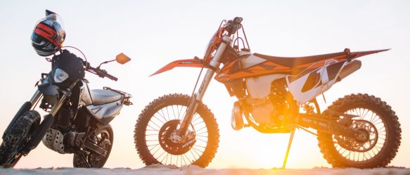 Two stationary motocross bikes with the sunset behind them.