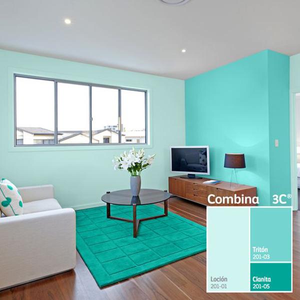 Mavi ve yeşilimsi mavi rengi duvarlarda ve dekorasyonda birleştiren bir oturma odası