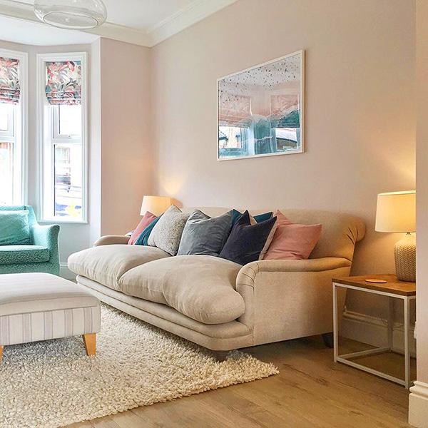 Pastel pembe tonlarında boyanmış ve dekore edilmiş bir oturma odası.