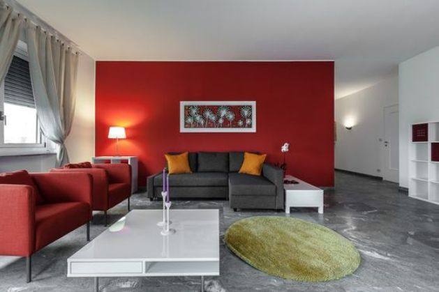 Gri kanepe ile birlikte duvarda kırmızı renk