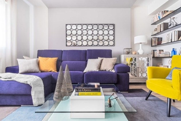 Mor bir kanepe ve sarı bir koltuk içeren küçük bir oturma odası