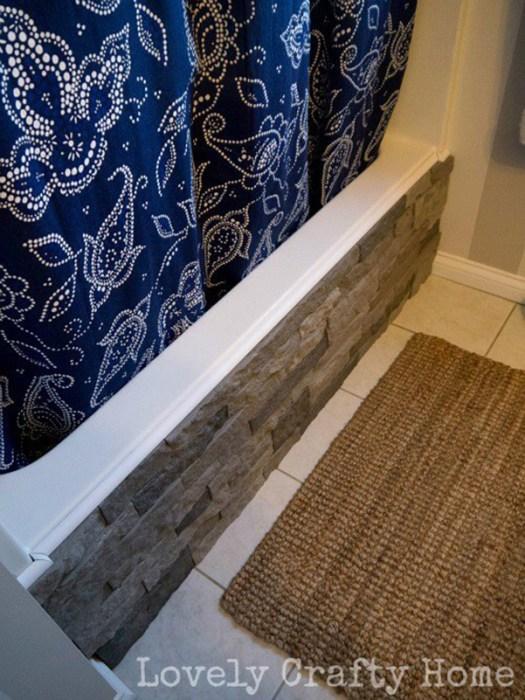 Bañera decorada con paneles de imitación a piedra