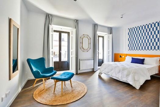 Dormitorio de matrimonio alegre y bonito en azul oscuro y naranja