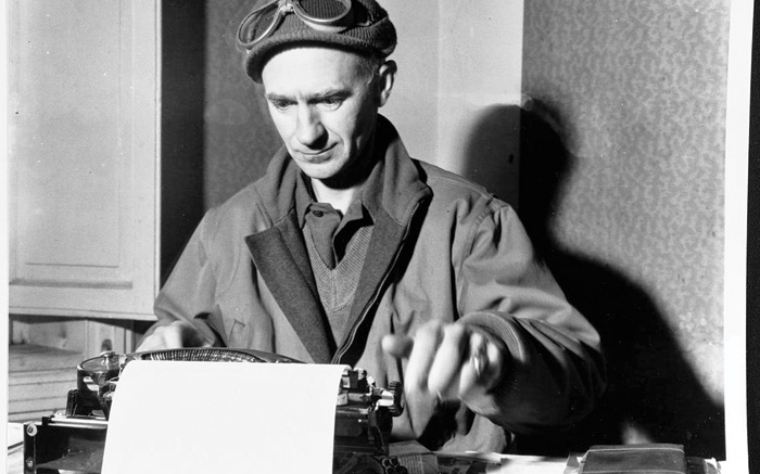 Black and white photograph of Ernie Pyle at work, sat at a typewriter.