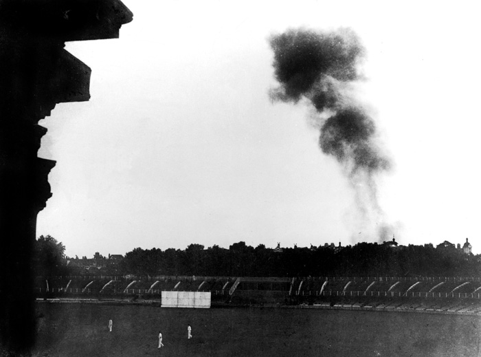 Smoke from a doodlebug rises over Lord's during a wartime match.