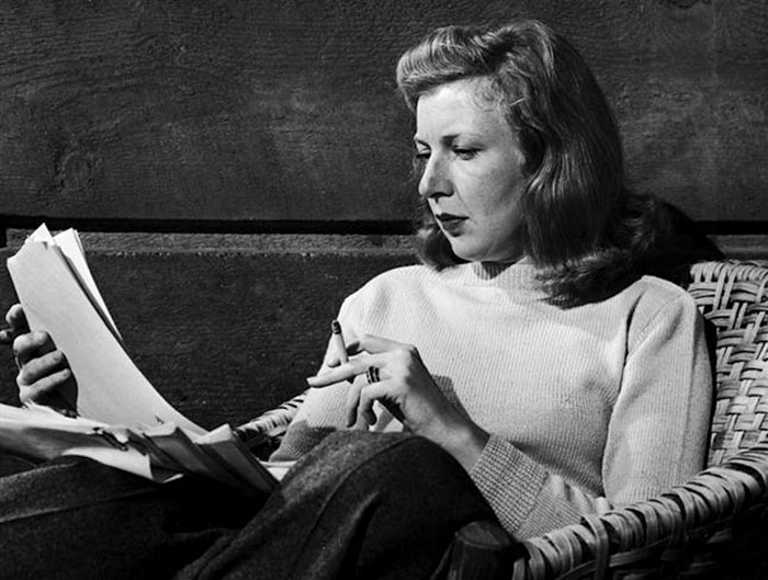 Black and white photograph of Martha Gellhorn - she is studying the sheets of paper in her right hand, while holding a cigarette between the fingers of her left hand.