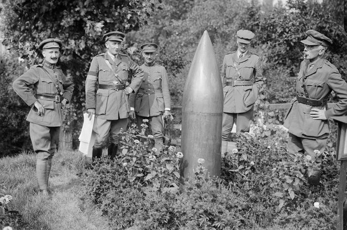 Five men in military uniform stand around a dud shell on the Western Front.