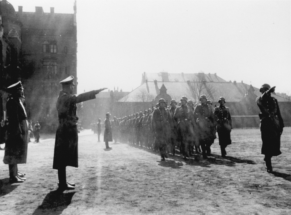 Members of Police Battalion 101 are saluted by their order police officers as they march in formation in Lodz. Image: United States Holocaust Memorial Museum, courtesy of Michael O'Hara; Bernhardt Colberg.