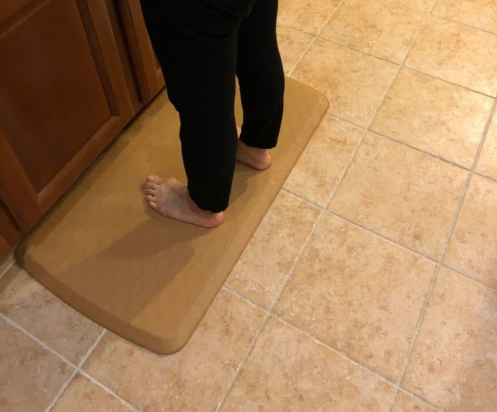 woman legs shown standing in kitchen on gelpro mat