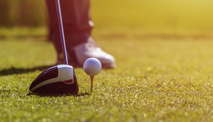Image of a man playing golf in green course. Focus on golf ball