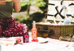 Image of lady sitting on picnic blanket with bottles and basket