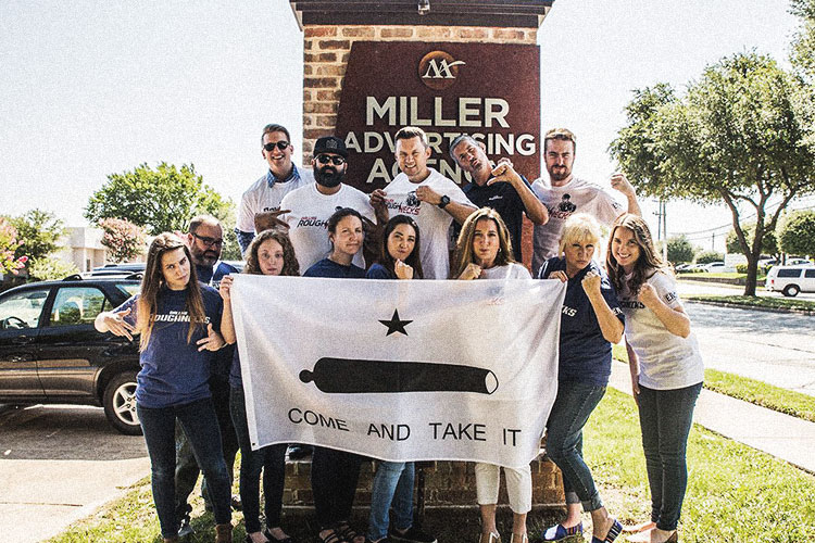 Tough Miller team with the come and take it flag by the Miller sign