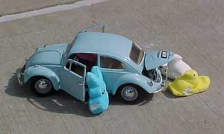 Photo of Peeps exiting a small VW Beetle