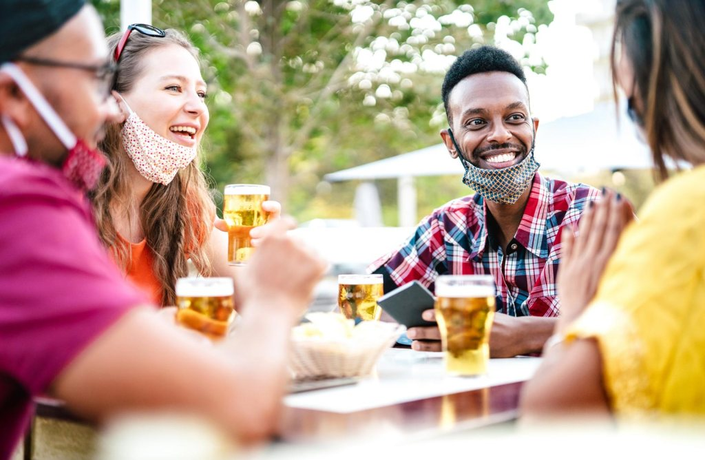 People drinking in beer garden with masks