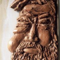 Bas-relief en terre cuite fixé sur un tableau en bois représentant la tête de Gargantua. Collection Milo Dias du Château de Roussillon.