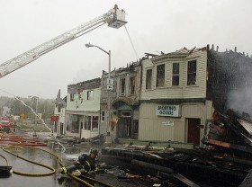 A firefighter is thrown to the ground after losing control of a high-powered hose while fighting the fire that consumed Milo's Main Street in September 2008.