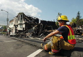 Milo firefighter Wayne Russell takes in the destruction of the town's Main Street, which was largely destroyed by arson in September 2008.