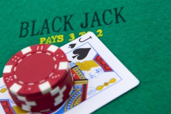 18443854 - black jack with red poker chips in the background.