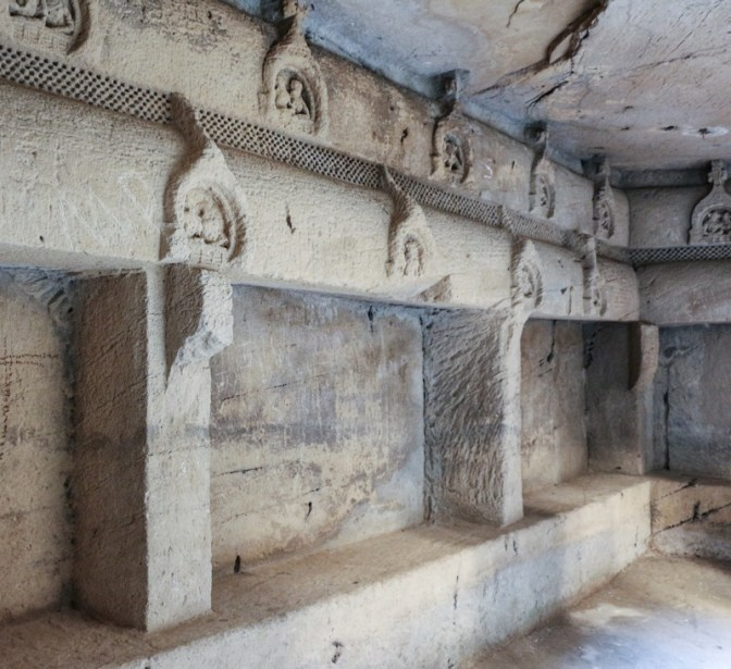 An interior wall with Chaitya Windows and benches