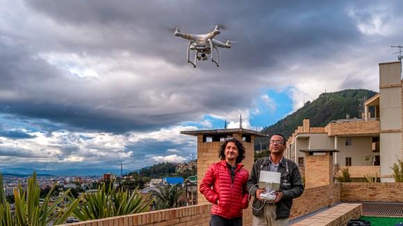 Un par de fotógrafos volando un dron desde la terraza de un edificio en Bogotá