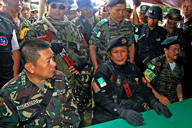 FRIENDS. MILF commander Abdurahman Macapaar, aka Kumander Bravo (center), and Col. Glen Macasero, commanding officer of the 103rd Infantry Brigade (left) during a press conference inside the rebel Camp Watu in Barangay Barit, Balindong town in Lanao del Sur Monday, Sept. 9. The MILF has allowed the Philippine Army to search their camps in Lanao del Sur following allegations that they were harboring terror groups responsible for the series of bombings in Cagayan de Oro City and other parts of Mindanao. No terror suspects were found in the camps. Mindanews Photo