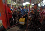 A police officer carries a ballot box as Army soldiers watch the gates at the Panderanao Primary School in Tugaya town in Lanao del Sur on Election Day, Oct. 28, 2013. MindaNews photo by Froilan Gallardo