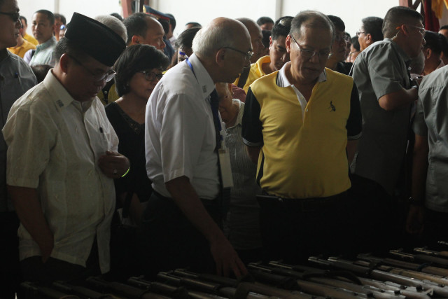 Moro Islamic Liberation Front chair Al Hadj Murad Ebrahim and President Benigno Aquino III inspect the firearms during a ceremonial turnover at the old Maguindanao provincial capitol in Sultan Kudarat on June 16, 2015. The MILF turned over a total of 75 weapons as an initial step toward decommissioning. MindaNews photo by Toto Lozano