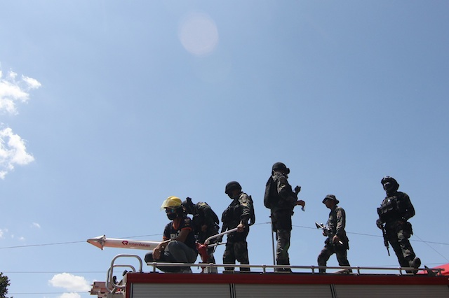 Members of SWAT (Special Weapons and Tactics) team on top of a firetruck in Kidapawan City on March 30, Day 1 of the barricade. MindaNews photo by TOTO LOZANO