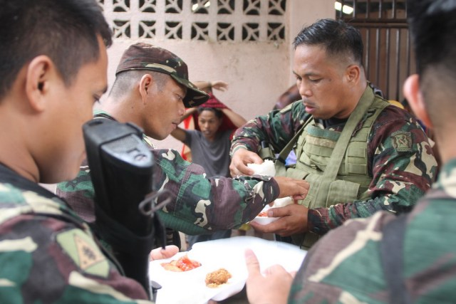 Soldiers take a late lunch after helping in the validation of evacuees from Marawi City at the covered court in Balo-i, Lanao del Norte on Tuesday, 30 May 2017. MindaNews photo by H. Marcos C. Mordeno
