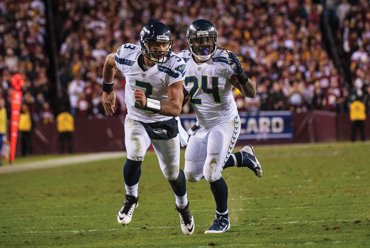 In an unusual move for a star quarterback Russell Wilson, #3, runs interference for running back Marshawn Lynch, #24.
