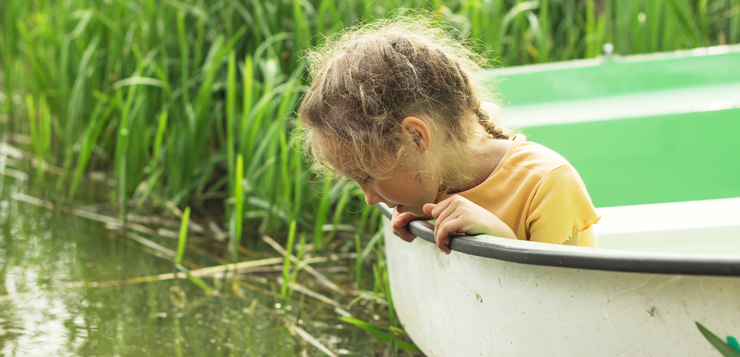 little girl looking into water from boat